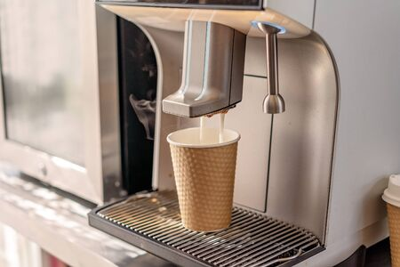 An automated coffee machine expelling a cappuccino into a paper takeaway cup