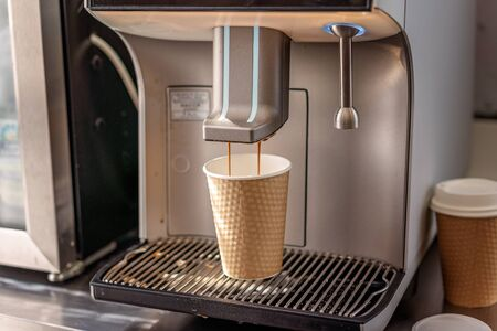 An automated espresso coffee making machine expelling a cappuccino into a paper takeaway cup Banco de Imagens