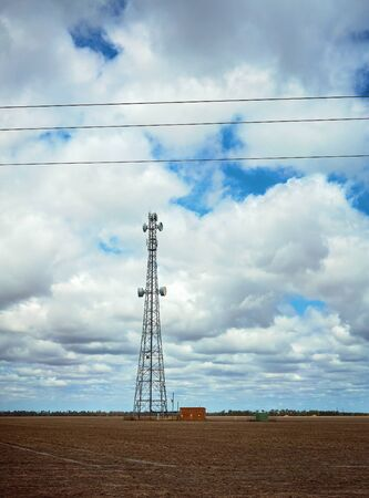A transmitting tower sitting in the midst of a barren Australian landscape, with stormy cloud background