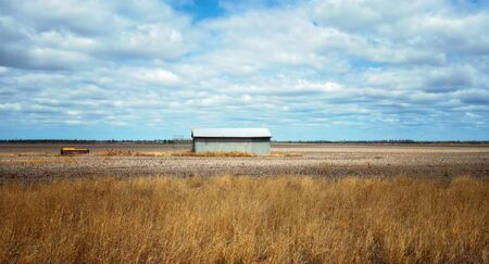 A lone tin shed standing in a dry brown Australian farm paddock suffering from a lack of rainfall