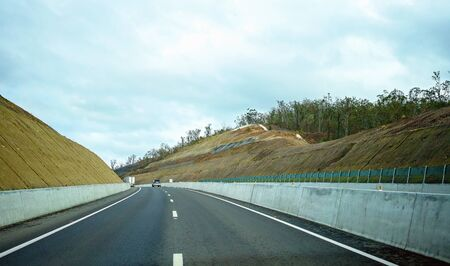 An Australian highway cut through a mountain pass with vehicles traveling ahead Stock Photo