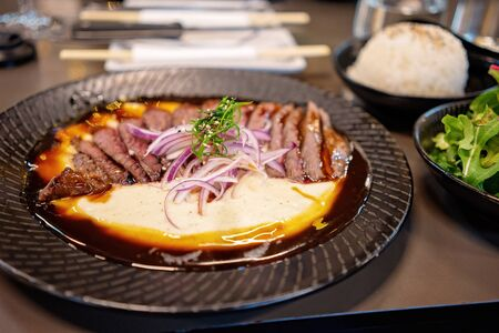 A dish of finely sliced wagyu steak with potato mash and sauce, accompanied by salad and rice