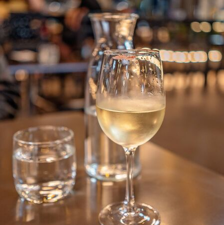 A glass of wine with a lipstick imprint on the rim against a warm glow background