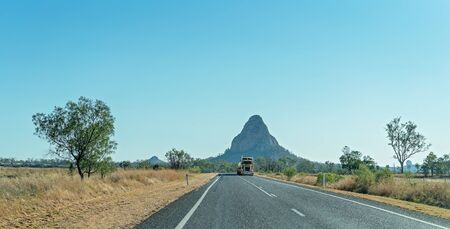 Clermont, Queensland, Australia - October 2019: A fuel tanker traveling along the highway in front of a mountain peak