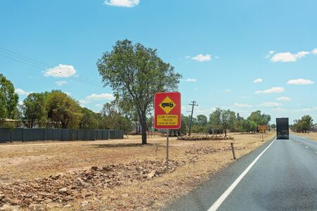 Clermont, Queensland, Australia - October 2019: Slow Turning Trucks warning sign on a country highway