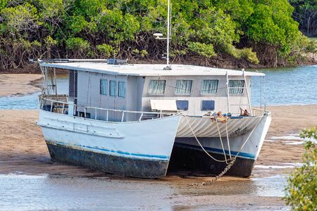 A catamaran boat stranded in the mud at low tide up a creek