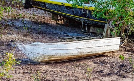 An old scratched dinghy lying on mangrove mud in front of a bigger boat
