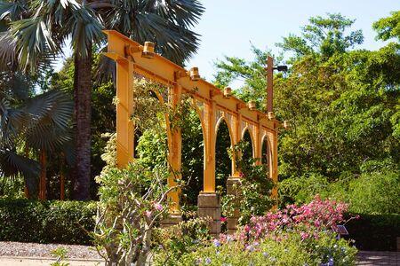 Arched decoration amongst landscaped botanic gardens on a bright sunny day