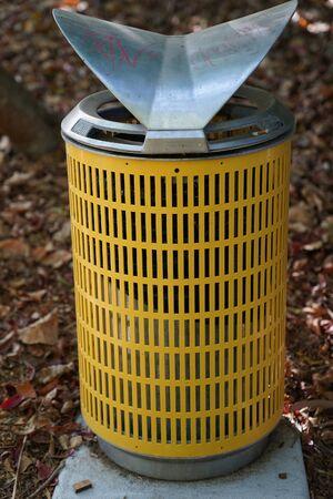 An outdoor yellow metal rubbish bin in a public park