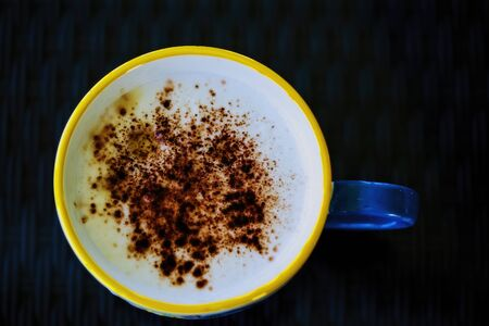Top view down onto a home brew cappuccino with sprinkled chocolate, on a dark background