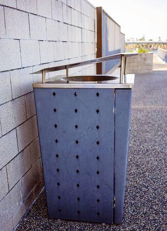 An outdoor blue metal rubbish bin in a public park