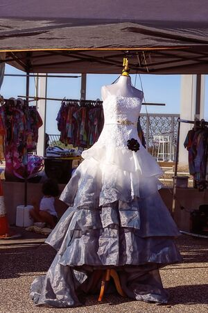 An elegant formal gown with an embroidered bodice and layers of chiffon on the skirt, featuring a beaded belt and a black rose, on sale at a market stall