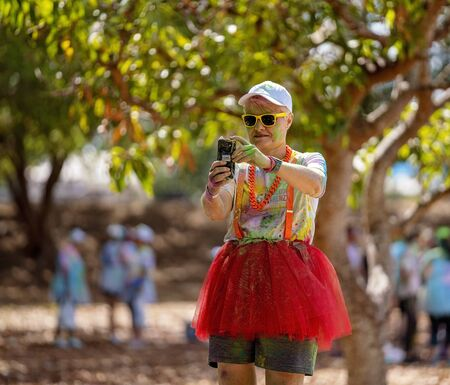 Mackay, Queensland, Australia - November 24th 2019: A colourfully dressed woman taking a selfie during the 5 K Colour Frenzy Fun Run outdoors in a public park