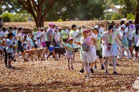 Mackay, Queensland, Australia - November 24th 2019: Unidentified people having fun in the 5 K Colour Frenzy Fun Run outdoors in a public park