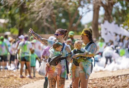Mackay, Queensland, Australia - November 24th 2019: Unidentified women and children taking selfies while participating in 5 K Colour Frenzy Fun Run outdoors in a public park