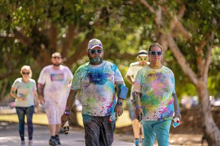 Mackay, Queensland, Australia - November 24th 2019: Unidentified couple walking in 5 K Colour Frenzy Fun Run outdoors in a public park
