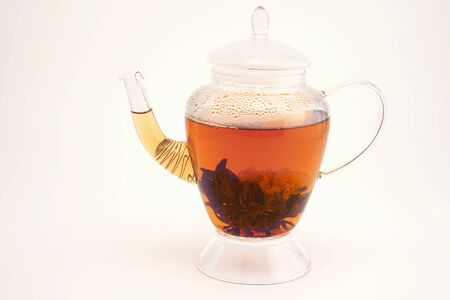 Blooming herbal tea blossom opened into a flower in a transparent glass teapot on a white background, with copy space