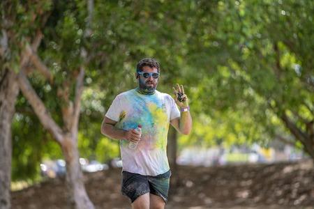 Mackay, Queensland, Australia - November 24th 2019: Unidentified beared man jogging in 5 K Colour Frenzy Fun Run outdoors in a public park