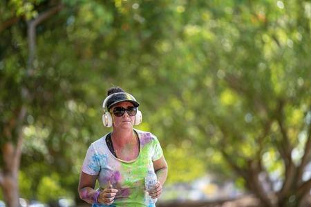 Mackay, Queensland, Australia - November 24th 2019: Unidentified woman jogging in the 5 K Colour Frenzy Fun Run outdoors in a public park