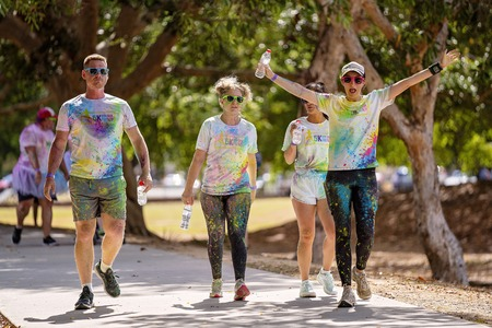 Mackay, Queensland, Australia - November 24th 2019: A group of unidentified friends splattered with coloured powder during the 5 K Colour Frenzy Fun Run outdoors in a public park