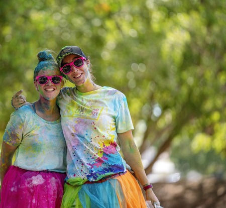 Mackay, Queensland, Australia - November 24th 2019: Two unidentified young women smiling and posing happily during the 5 K Colour Frenzy Fun Run outdoors in a public park Publikacyjne