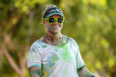 Mackay, Queensland, Australia - November 24th 2019: A smiling unidentified woman running in the 5 K Colour Frenzy Fun Run outdoors in a public park Publikacyjne