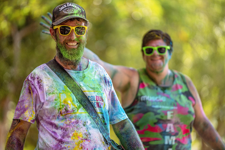 Mackay, Queensland, Australia - November 24th 2019: A smiling and happy unidentified couple fooling around in the 5 K Colour Frenzy Fun Run outdoors in a public park