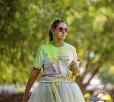 Mackay, Queensland, Australia - November 24th 2019: An unidentified woman walking in the 5 K Colour Frenzy Fun Run outdoors in a public park