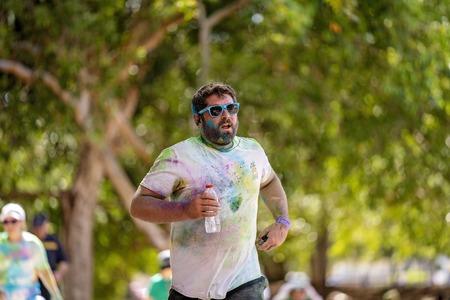 Mackay, Queensland, Australia - November 24th 2019: An unidentified man jogging in the 5 K Colour Frenzy Fun Run outdoors in a public park