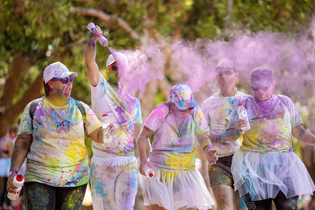 Mackay, Queensland, Australia - November 24th 2019: Man sprinkling pink powder over an unidentified group of people in the 5 K Colour Frenzy Fun Run outdoors in a public park Publikacyjne