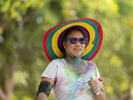 Mackay, Queensland, Australia - November 24th 2019: A smiling unidentified woman in a colourful straw hat jogs in the 5 K Colour Frenzy Fun Run outdoors in a public park