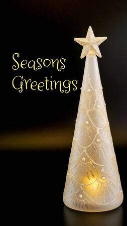 A glittering opaque glass Christmas tree with a star on top, lit from within and against a black background, Seasons Greetings message, suitable for web, greeting cards etc