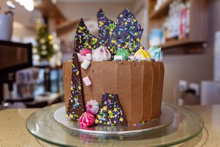 A home made birthday cake with chocolate frosting, shards of colourful chocolate, and glittering meringues