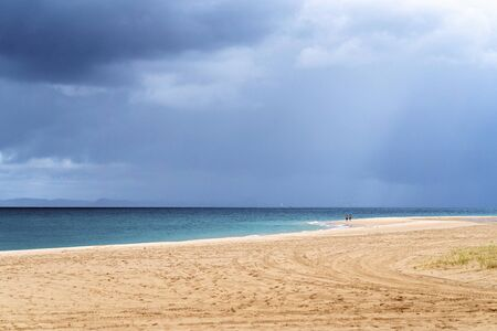 An unidentifiable couple walk along the sandy beach of an Australian island while storm clouds gather overhead