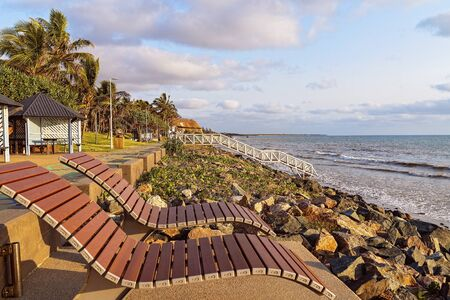 Timber deck chairs above the beach for people to relax and enjoy the views. At A small seaside town in Australia.