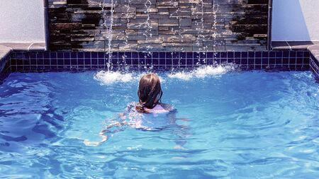 Young caucasian girl with long blonde hair swimming towards a fountain in a hotel pool