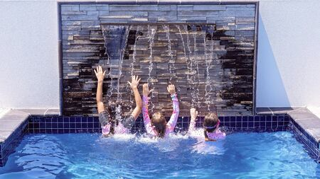 Three young girl cousins playing under a waterfall in a hotel swimming pool while on holidays together Foto de archivo