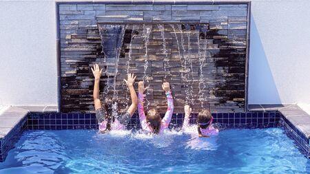 Tres primos de niña jugando bajo una cascada en la piscina de un hotel durante las vacaciones juntos Foto de archivo