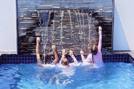 Tres primos de niña jugando bajo una cascada en la piscina de un hotel durante las vacaciones juntos