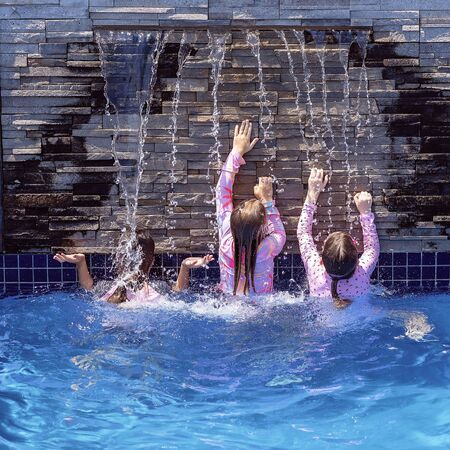Three young girl cousins playing under a waterfall in a hotel swimming pool while on holidays together