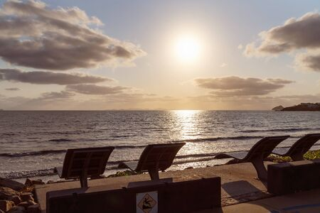 Timber chairs above the beach for people to recline and relax and watch the ocean activities and enjoy the views. Image taken just after sunrise, in a small seaside town in Australia.