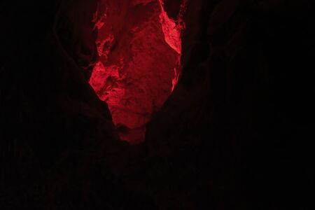 Inside Australia's bat ecotourism Capricorn Caves, glowing red in an expanse of darkness and extreme low light