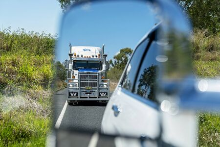 Waverley Creek, Queensland, Australia - December 2019: A semi trailer truck driving on the highway as seen through the rear vision mirror of the car in front