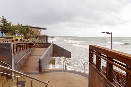 Capricorn Coast Australia - A walkway and viewing deck on the coast at high tide on a cloudy day Stock Photo