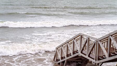 Capricorn Coast Australia - Stairs down to the beach being lapped by waves at high tide Stock Photo