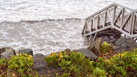 Capricorn Coast Australia - Stairs down to the beach being lapped by waves at high tide Stockfoto
