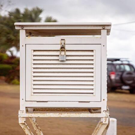 A locked white wooden weather meter box standing in a car park