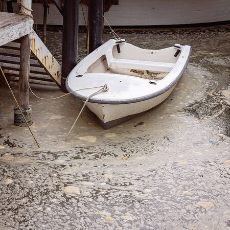 A small white row boat tied up to a post in swirling foamy dirty water at an old timber jetty piled with rubbish