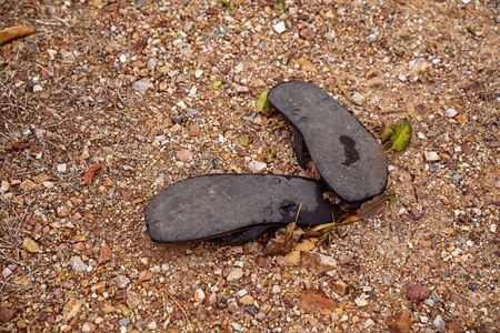 A pair of discarded old rubber thongs lying in the dirt - typical Australian footwear
