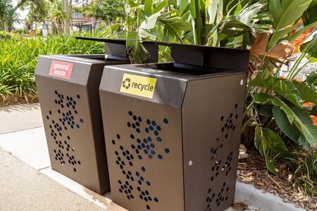 General waste and recycle rubbish bins beside a garden in a public outdoor recreational park